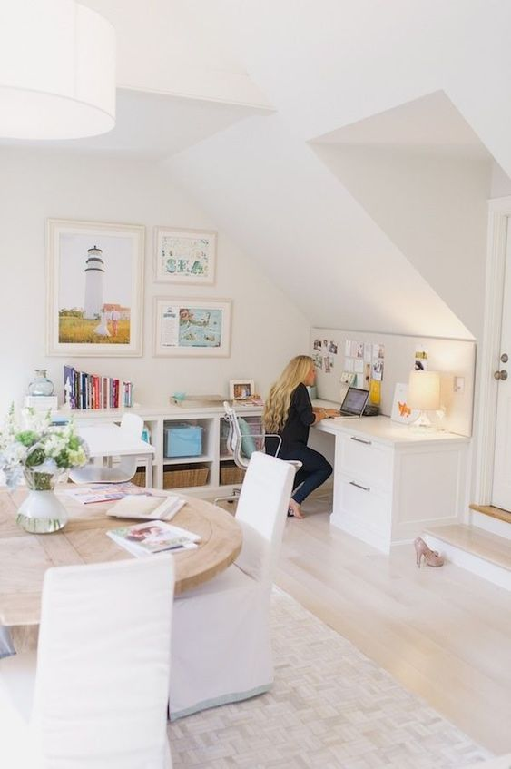 a neutral attic home office with a large L-shaped desk, a gallery wall, a round table, colorful books and baskets