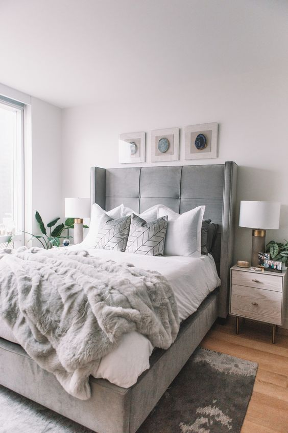 a neutral bedroom infused with soft greys - an upholstered grey bed, a fur rug and lamps, a fur blanket