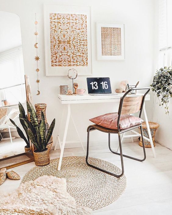 a neutral boho home office with a gallery wall, a small desk, a pink chair, layered rugs and potted greenery