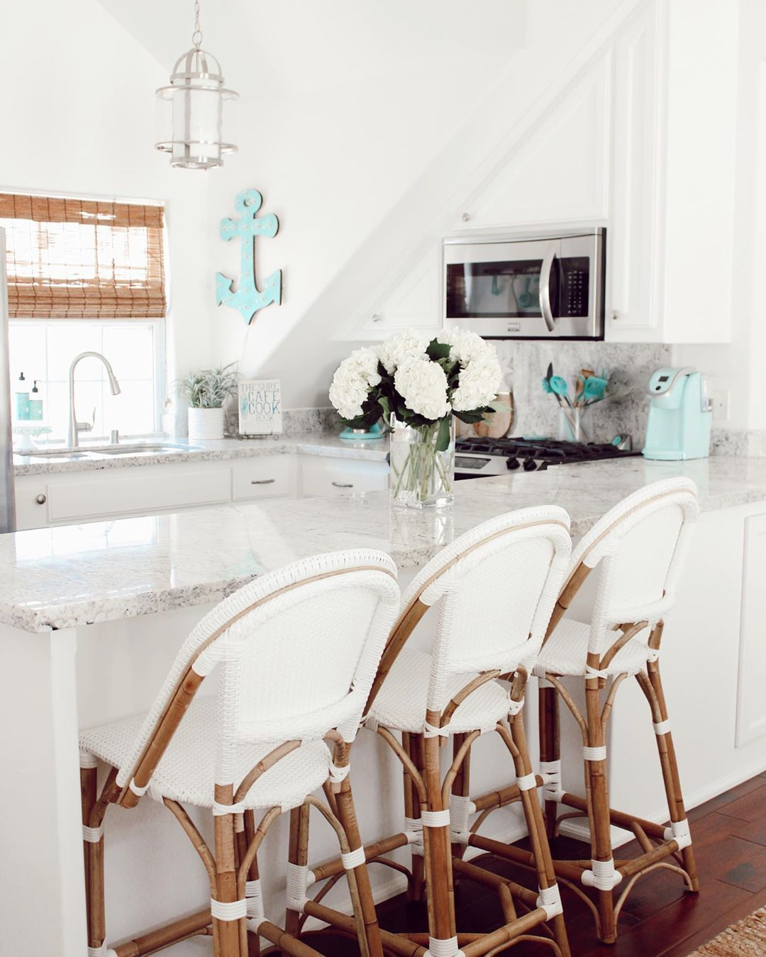 a neutral coastal kitchen with white cabinetry, a grey stone countertop, woven shades, a light blue anchor and rattan chairs