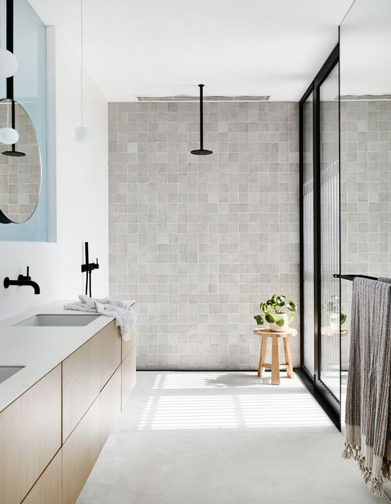 a neutral contemporary coastal bathroom with a floating wooden vanity, a grey tile wall, black touches for some drama
