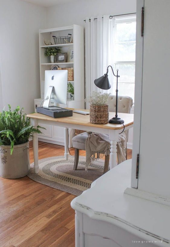 a neutral farmhouse home office with a vintage desk, a black table lamp and a computer stand, a vintage chair and lots of ferns