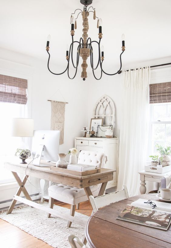 a neutral farmhouse home office with a wooden trestle desk, a vintage chandelier, woven shades, a macrame hanging and neutral textiles