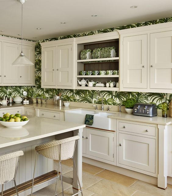 a neutral farmhouse kitchen with creamy cabinets, tropical print wallpaper, creamy woven chairs and pendant lamps