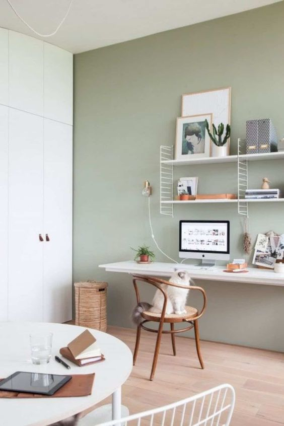a neutral home office with an olive green accent wall, a floating desk, a shelf and baskets and a wooden chair