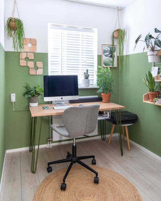 a neutral modern home office with color block green walls, mid-century modern furniture, potted plants and wooden decor