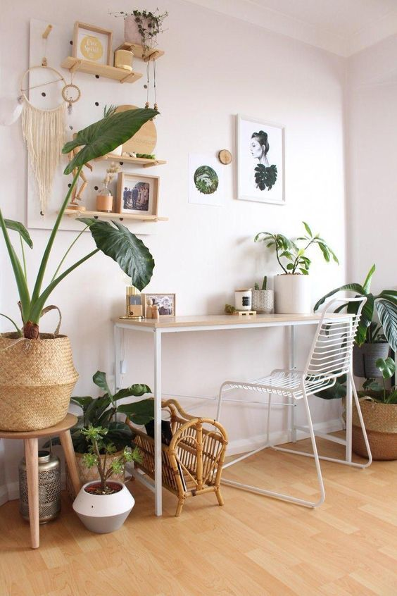 a neutral tropical boho home office with white furniture, a pegboard with a dreamcatcher and various decor plus potted plants
