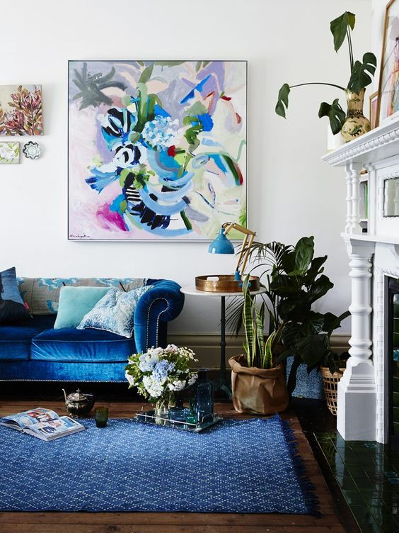 a neutral vintage-inspired living room infused with color - a bold blue sofa and rug, a colorful artwork and some more blue touches