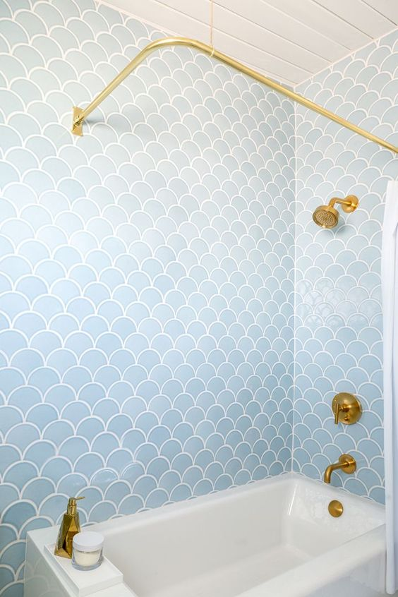 a pale blue bathroom clad with fishscale tiles and accented with gold looks refined and stylish