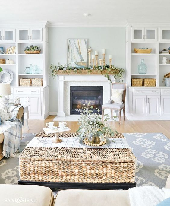 a pastal coastal living room with aqua walls, neutral furniture, a woven coffee table, greenery and candles