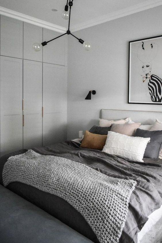 a peaceful contemporary bedroom with dove grey walls and a storage unit, grey bedding with touches of blush and a statement artwork