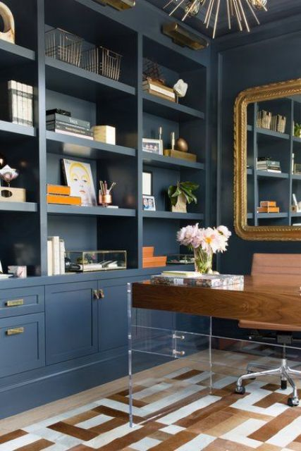 a preppy navy home office with built-in storage units, a wood and acryl desk, a gold framed mirror and a sunburst chandelier