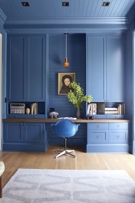 a pure blue home office with built in storage units, open and closed ones, a floating desk and a blue chair is a statement in itself
