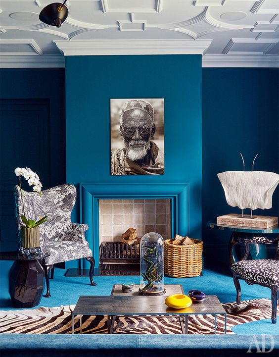 a refined and catchy living room with classic blue walls, a matching sofa and a side table plus statement prints