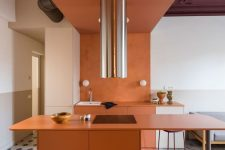 a refined burnt orange kitchen with sleek matte cabinets, white ones, a burnt orange roof and a shiny metal hood