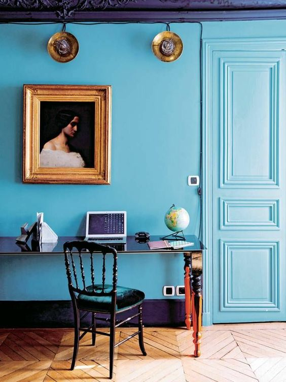 a refined eclectic blue home office with a chic desk, a velvet chair, a vintage artwork and modern accessories
