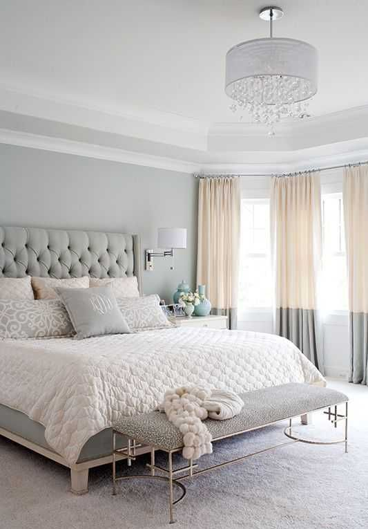 a refined grey bedroom with dove grey walls, a grey bed and bench, color block curtains and a crystal chandelier