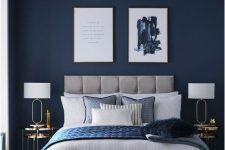 a refined modern bedroom with navy walls, a grey upholstered bed, chic artworks, gold nightstands and blue bedding