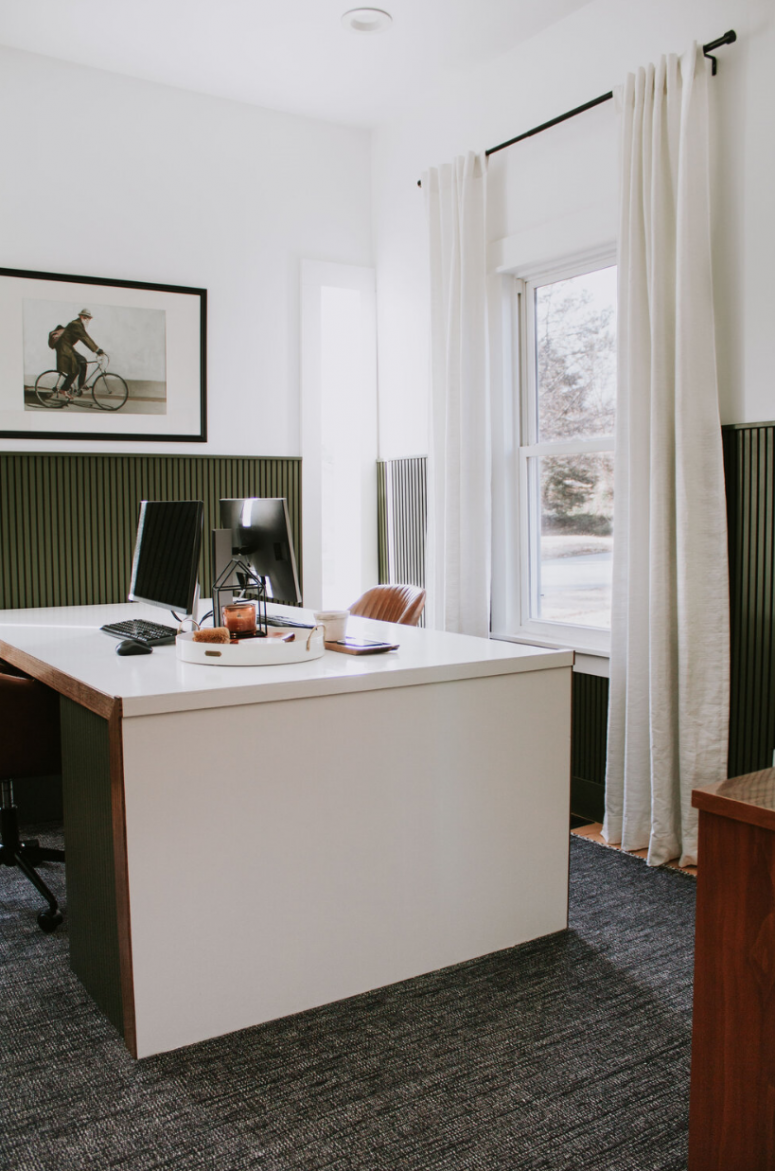 a refined modern double home office with sage green wooden planks on the walls, a chic color block desk, leather chairs and a statement artworkk