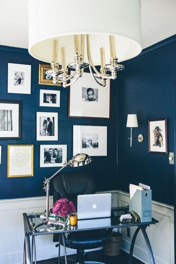 a refined modern navy home office with a gallery wall, a glass desk, a leather chair and chic lamps