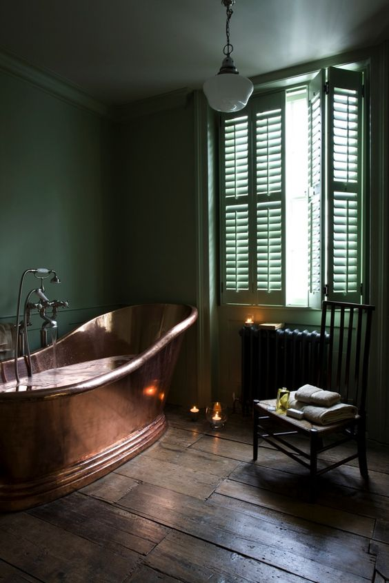 a refined moody bathroom in green, with a black radiator, a copper bathtub and candles around is very chic