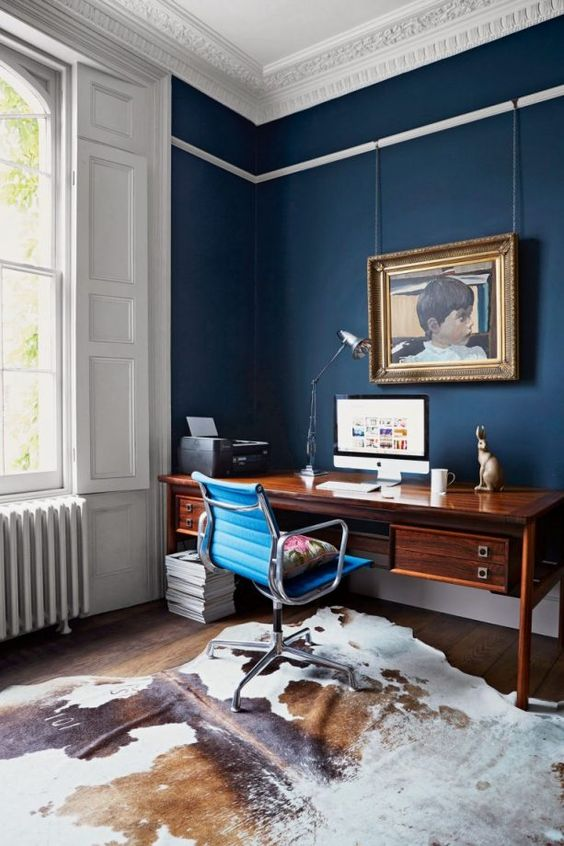 a refined navy home office with a vintage rich stained desk, a modenr blue chair, a cowhide rug, a vintage artwork and a simple lamp