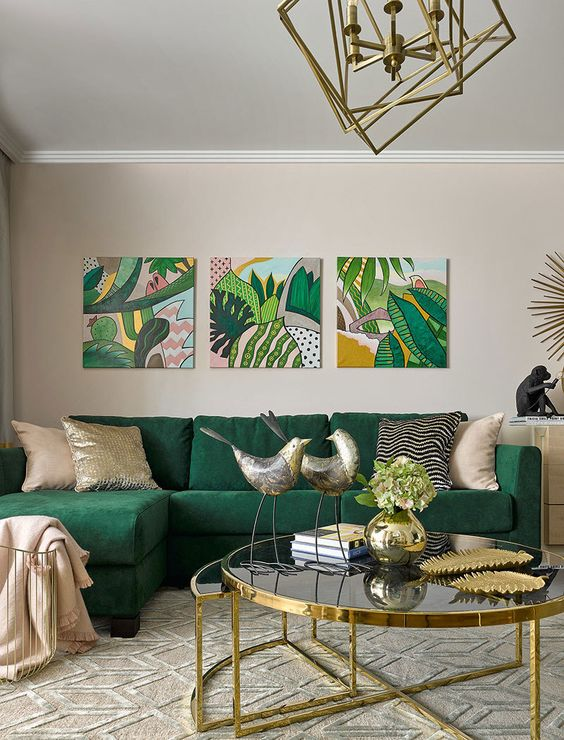 a refined tropical living space with an emerald sofa and bright artworks plus touches of gold is chic