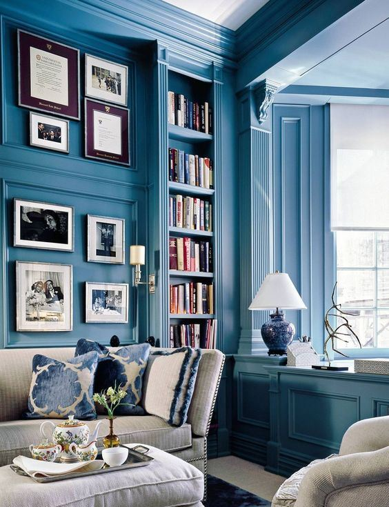 a refined vintage blue living room with light blue walls, molding, neutral furniture and large windows