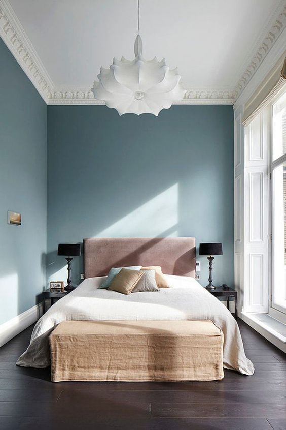 a refined yet minimal bedroom with blue walls, a ceiling with molding and a glazed wall, a pink bed and an upholstered bench