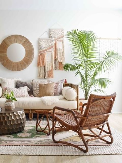 a relaxed boho tropical living room done in neutrals, with rattan furniture, woven and fringe wall hangings and a statement plant