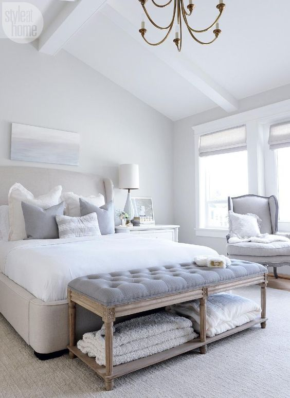 a relaxing dove grey bedroom with a grey upholstered bed, grey upholstered furniture, a vintage chandelier and a coastal artwork