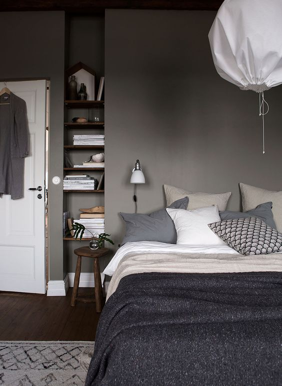 a relaxing grey bedroom - grey walls, dark stained furniture, grey and white bedding create a moody yet peaceful place to be