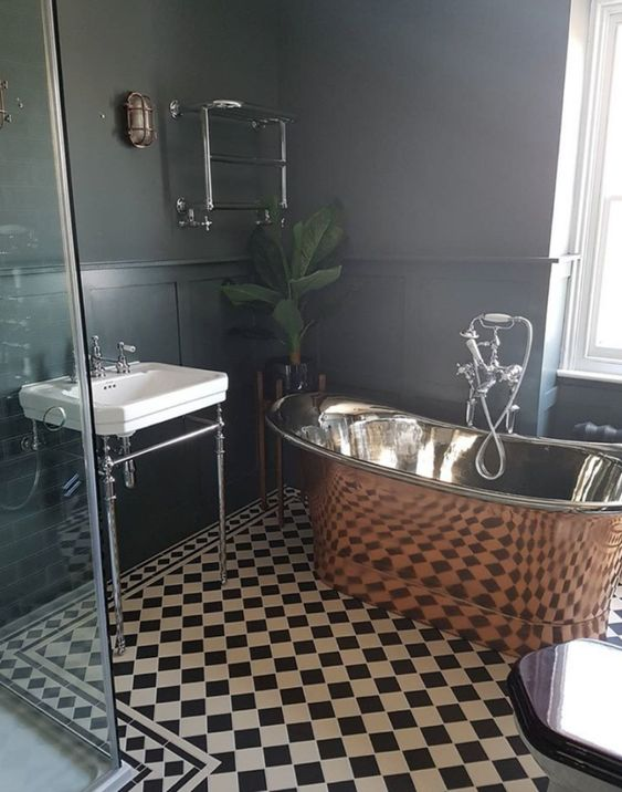 a retro inspired black and white bathroom spruced up with a gorgeous vintage copper tub and a potted plant