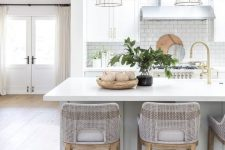 a romantic coastal kitchen with dove grey and white cabinetry, a large kitchen island with a meal space, grey stools and glass lamps
