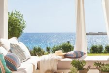 a romantic coastal porch with a large L-shaped sofa, colorful linens, curtains for privacy and a fantastic sea view