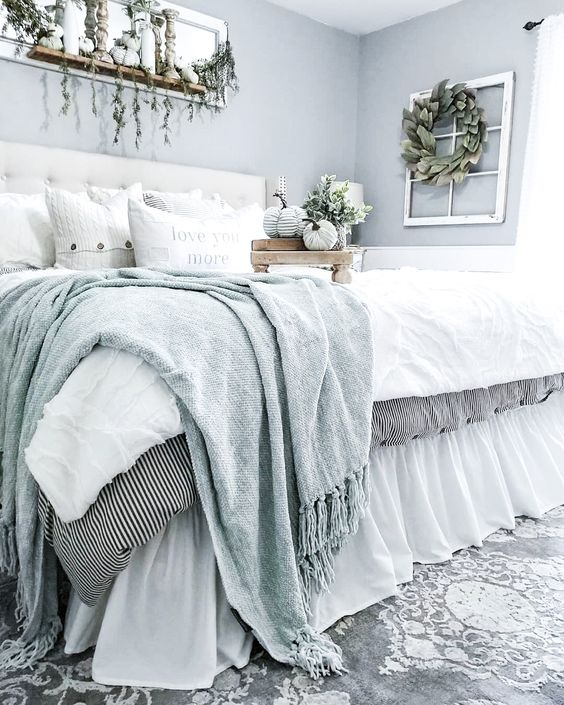 a romantic modern farmhouse bedroom with light blue wlals, a white leather bed, chic neutral and light blue bedding and a shelf with pumpkins and cascading greenery