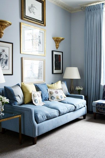 a romantic pastel blue living room with everything in light blues and a chic gallery wall with gold touches