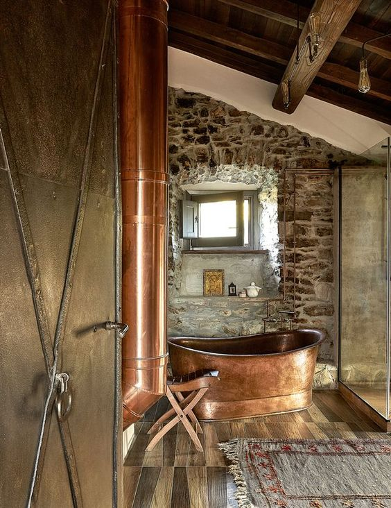 a rustic bathroom with stone walls, wooden beams and a floor, a free-standing copper bathtub and copper fixtures is cozy