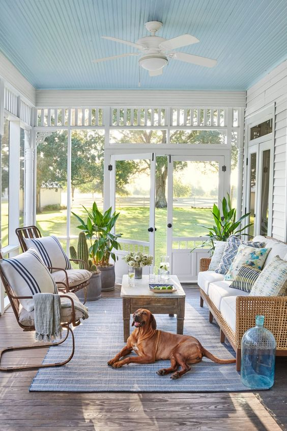 a screened beach porch with rattan and wicker furniture, printed textiles, a wooden table and a blue rug plus potted plants
