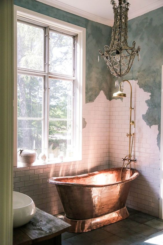 a shabby chic bathroom with green and white tile walls, a luxurious copper tub and a crystal chandelier