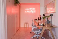a shared millenial pink home office with a pink accent wall with neon, pink and white hex tiles and neutral furniture