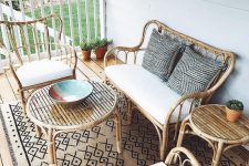 a simple and chic coastal porch with rattan furniture, neutral textiles and a boho printed rug is lovely