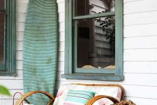 a simple and lovely beach porch with a large rattan chair with colorful textiles, a turquoise fabric covered surf board and a basket with firewood