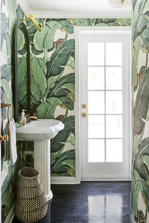 a simple and small powder room with banana leaf wallpaper, white appliances and touches of gold
