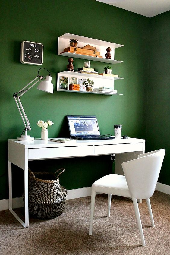 a simple and stylish contemporary home office with green walls, white furniture and a basket as a trash bin