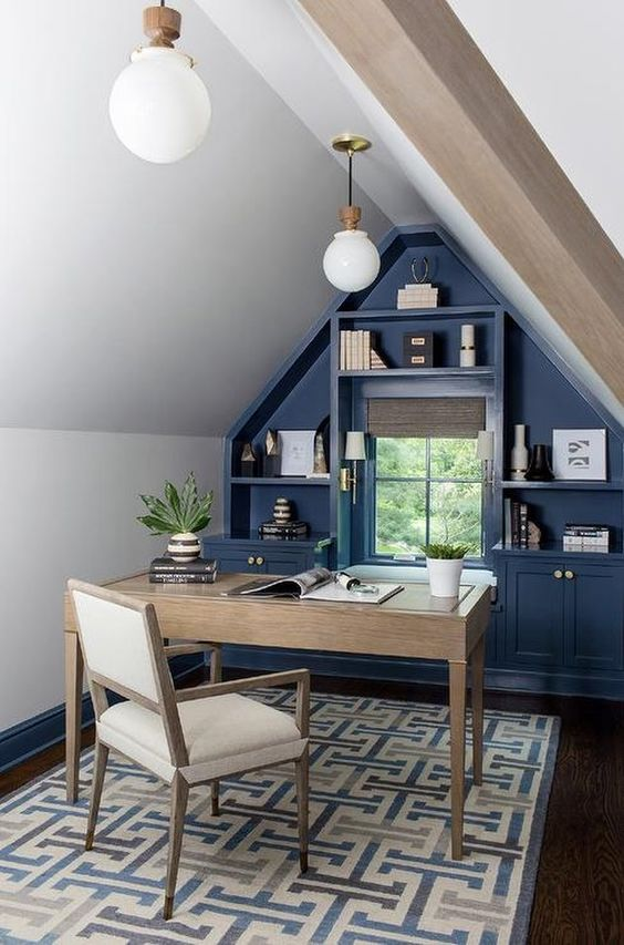 a small attic home office in neutrals, with a blue storage unit that takes a wall, simple neutral furniture