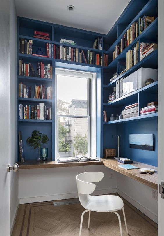 a small blue home office with shelves that take the whole space, a floating wooden desk and a white chair