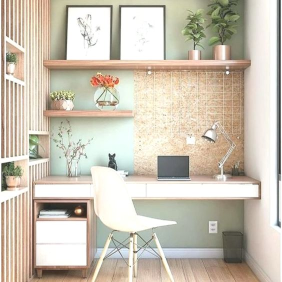 a small home office nook with a sage green wall, floating shelves and a desk, a white chair and a wood slab divider