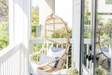 a small neutral coastal porch with a hanging rattan chair with blue pillows and a white side table plus a view