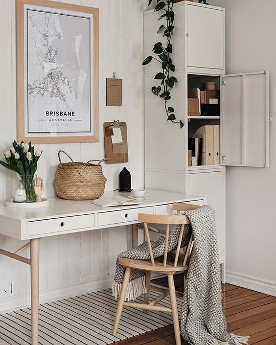 a small neutral home office with modern furniture, potted plants, a gallery wall and a basket